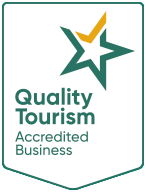 Australian Tourism Accreditation Program logo. Green shield with 5 pointed white star in top right corner. The top point of the star is coloured gold resembling a gold tick of approval. The words Quality Tourism Accredited Business are below the star.