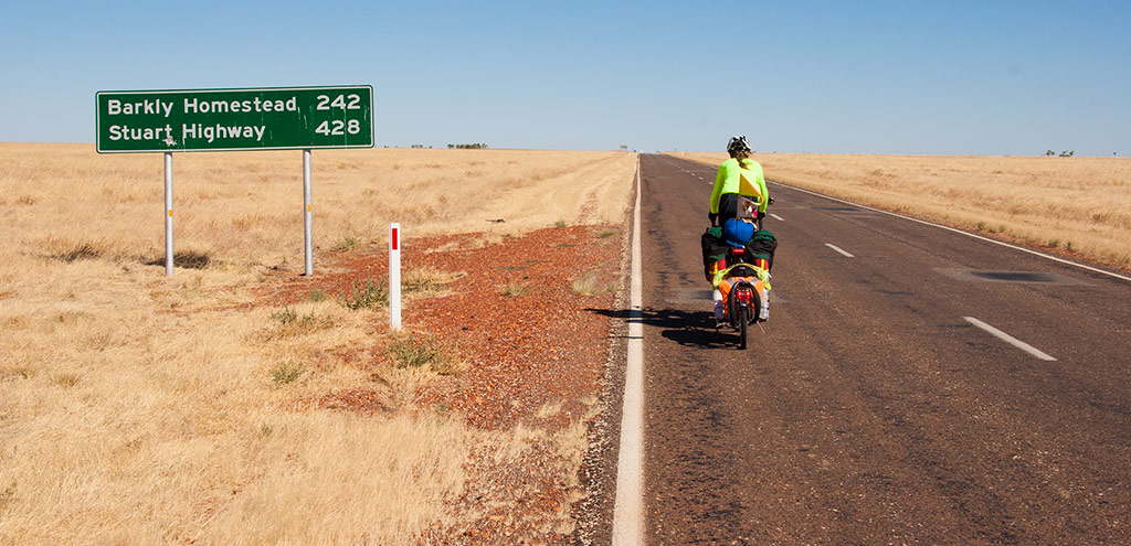 "The road sign is at the beginning of a very slight uphill climb and reads ""Barkly Homestead 242, Stuart Highway 428"". The road is straight and surrounded by short dry golden grass. A cyclist is towing a fully loaded BOB trailer  towards the sign."