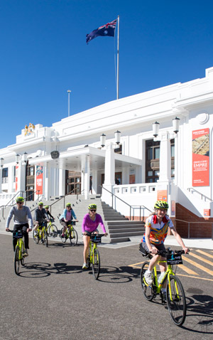 6 cyclists on a Canberra Bike Tour pass by the front steps of Old Parliament House. The Australian flag flies in a cloudless blue sky. The building is white.