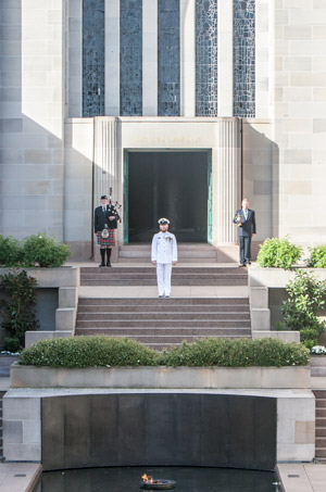 An Australian Naval Officer in white uniform stands to attention in front of the open doors to the Hall of Memory. A piper stands behind at the left of the image and a bugler stands behind to the right of the image.