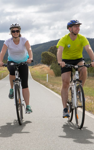 A female and a male ride their bikes on a grey bitumen road on a bike ride to Tidbinbilla Nature Reserve