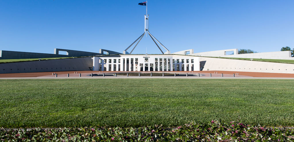 The front entrance to Australia's Parliament House. The large 81 metre tall stainless steel flagpole flies a flag  the size of two double decker buses.