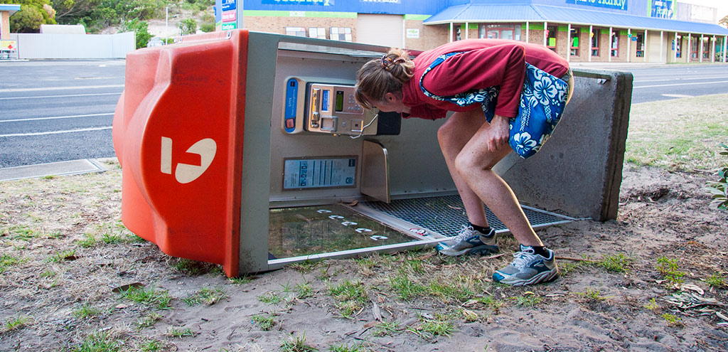 Woman answering the telephone in a fallen Telstra telephone booth in Robe, South Australia