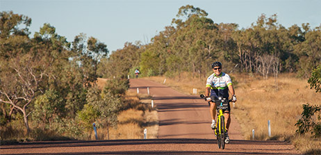 Man on an outback cycling tour riding a bicycle towards the camera. The sealed road is topped with red granite bitumen. Long shadows indicate the end of the day. Salmon glow on trees and grass from setting sun. Blue cloudless sky.