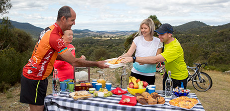 In front of views of the Tidbinbilla Valley. Table covered with a blue and white table cloth and large plates of savoury food and cakes and hot and cold drinks. Four people on a bike tour help themselves to the food. Cloudy skies.