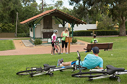 A male cyclist relaxes beside two bicycles which are lying on the grass in front of the reconstructed Changi Chapel whilst two female cyclists read the visitors book.