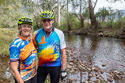 A male and female cyclist both in colourful cycling jerseys and fluoro yellow bicycle helmets stand on a bank of smooth river stones beside the King River. Eucalypt trees are on each side of the river bank.