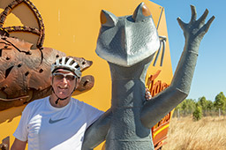 A man in a white t-shirt and white bicycle helmet stands with his arm around the shoulders of a very tall Gilbert's Dragon lizard that is standing on its hind legs. The lizard is waving with its left front leg.