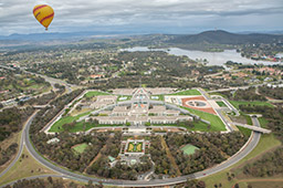 The Australian Parliament House as viewed from a hot air balloon. A yellow and red-striped hot air balloon is in the sky to the left. Views of Lake Burley Griffin and Canberra City are in the background. Overcast skies.