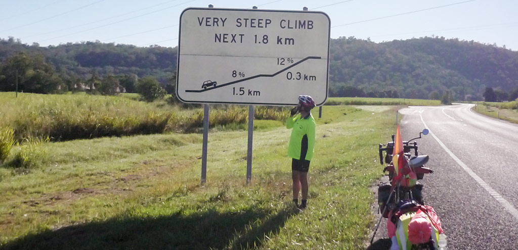 "A cyclist with a bicycle and loaded BOB trailer stands beside a road sign with the words ""Very steep climb next 1.8km"" with a diagram indicating 1.5km at 8% and 0.3km at 12%."