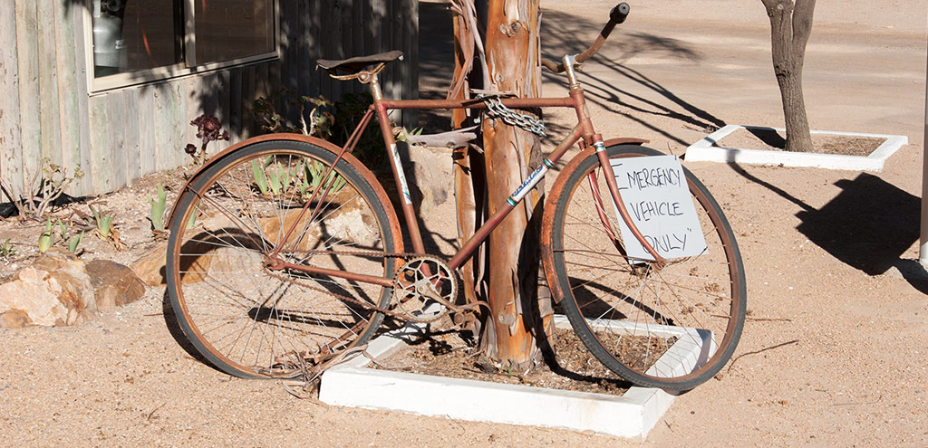 "A rusting bicycle with an old leather saddle chained to a tree with the sign ""Emergency Vehicle Only"""
