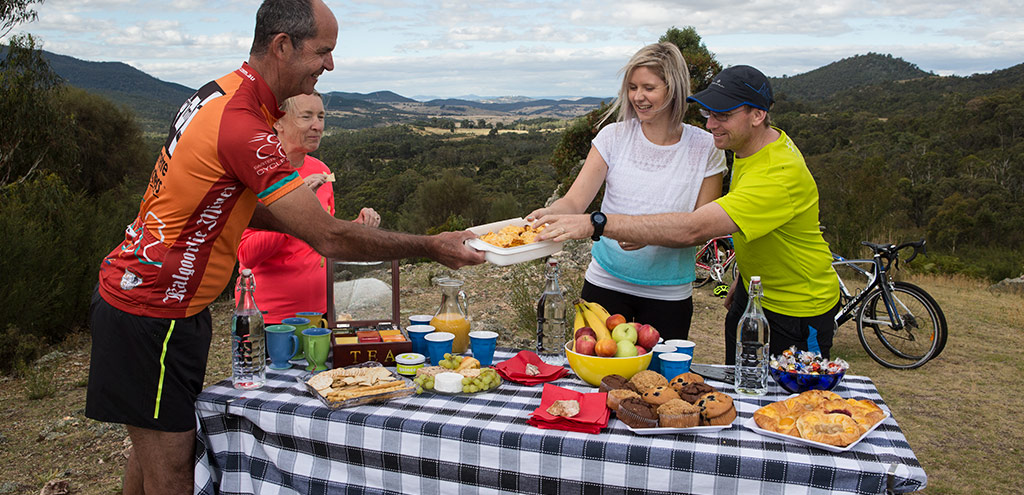 In front of views of the Tidbinbilla Valley four cyclists help themselves to a table spread with snacks, cakes and drinks.