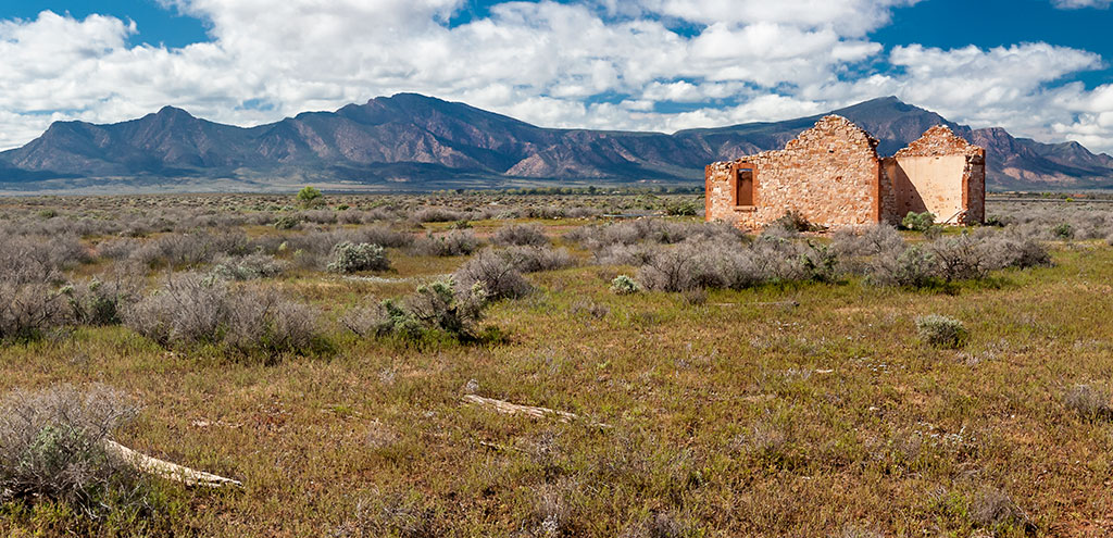 A ruined creamy stone railway building without a roof. The Flinders Ranges dominate the background. A row of rotting wooden railway sleepers mark the location of the old railway line in the foreground.