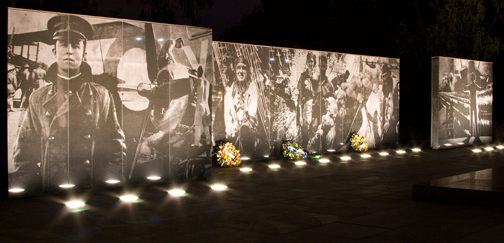 A polished granite wall with photographs illuminated by lights in the footpath.