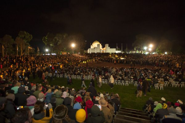 Large numbers of people both seated and standing around the Parade Ground and Stone of Remembrance in front of the Australian War Memorial.