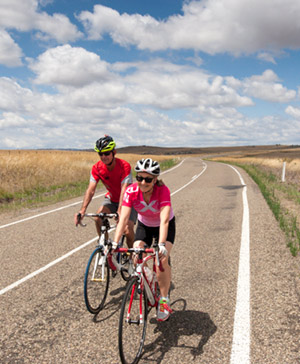 Two road cyclists dressed in red on a bike ride on a sealed bitumen road. Long yellow/gold grass either side of the road, cloudy blue sky.