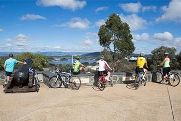 Five cyclists on top of Mt Pleasant admire the view of Canberra. The Royal Australian Artillery Memorial consists of a stone parapet with concrete panels recording the campaigns in which the Royal Regiment of Australian Artillery took part and an obelisk flanked by two cannons. Some buildings of the Russell Offices Defence complex are visible below the left-hand cannon. Lake Burley Griffin Central Basin, the Australian-American War Memorial, Canberra City buildings, and the Black Mountain Tower (Telstra Tower) are also visible.