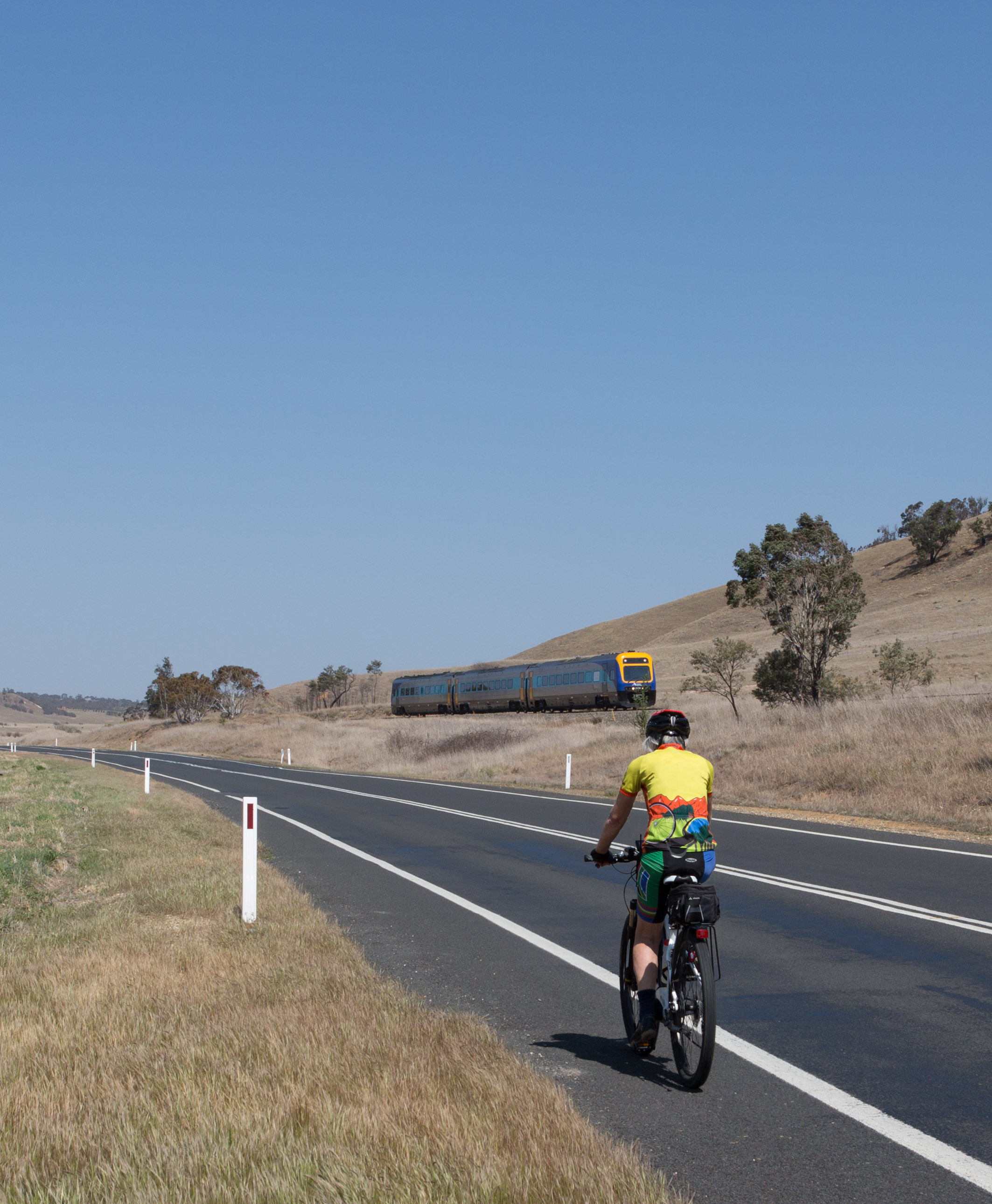 One of our cyclists on the road to Tarago with the Canberra to Sydney XPT heading towards Sydney.