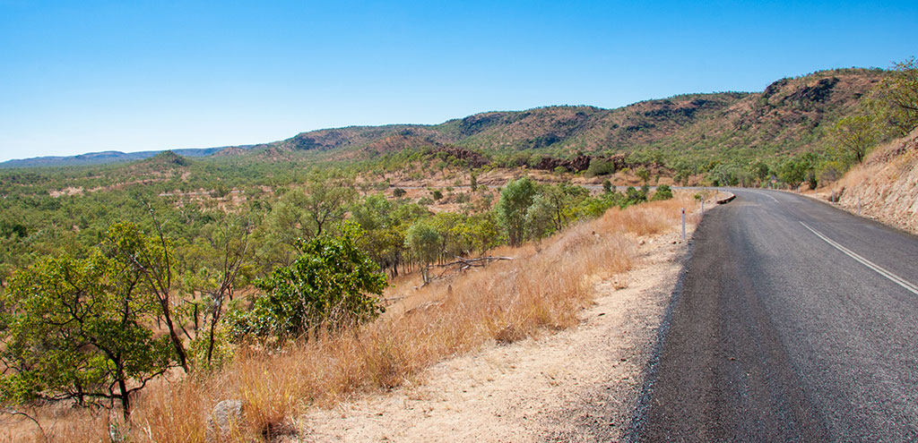 Under a blue sky a grey bitumen road winds its way through the red soils and rocks covered with dry grass and dotted with vibrant green trees.