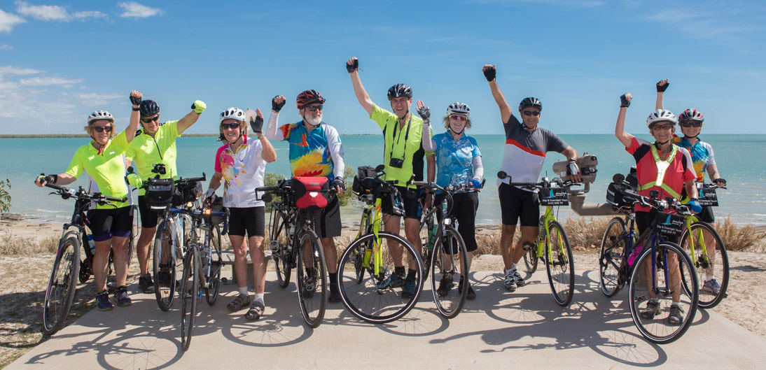 9 cyclists with hands raised standing in front of blue Gulf of Carpentaria