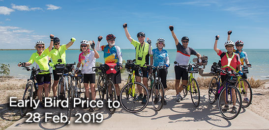 9 cyclists with hands raised are standing next to their bicycles at the end of their bike ride. The very blue Gulf of Carpentaria stretches to the horizon behind them. Blue sky with a few thin white clouds.