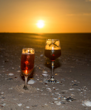 Two wine glasses sit on the sand with the sun setting behind them. This is how we conclude our Cairns to Karumba bike ride.