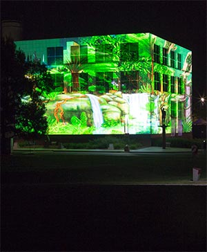 An illustrated green tropical forest scene including ferns and a flowing creek is projected onto the corner of the white building.