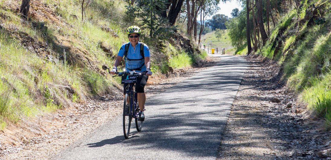 A cyclist rides through a cutting  between Everton and Beechworth
