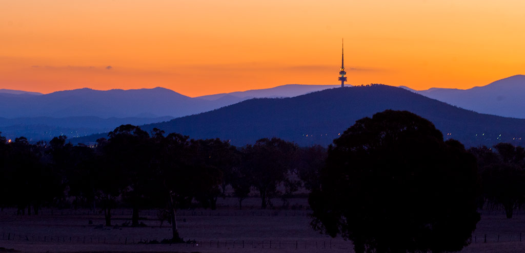 A deep orange sky above the purple silhouette of the mountains and the Black Mountain Tower. Small specks of light are seen from the suburbs.