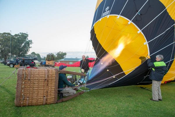 A wicker balloon basket is laying on its side. A man is directing the burners and large flame into the mouth of a black and yellow balloon. 2 people hold the mouth of the balloon open.