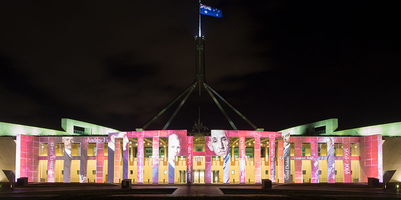 Photographs of past Australian Prime Ministers, their names and years of service are projected onto the front of the Parliament House. The large Australian flag flies from the stainless steel flagpole over the house. Black night sky.