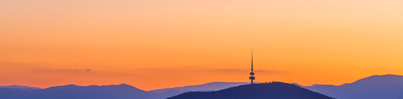 Silhouette of Black Mountain Tower against orange cloudless sky above purple mountains.