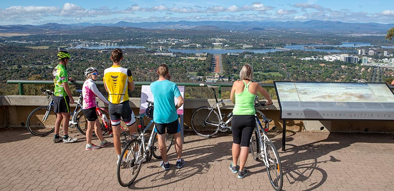 Under blue skies, 5 cyclists stand with their bikes behind the Marion Mahony Griffin View handrail. The Australian War Memorial can be seen just behind with ANZAC Parade leading to Lake Burley Griffin and both 'Old' white and 'New' Parliament Houses behind. Canberra City can be seen in the middle right.