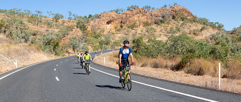 Five cyclists enjoying the descent of the Newcastle Range on a well formed bitumen section of National Highway 1 or Gulf Development Road. Orange red cliffs are in the background.