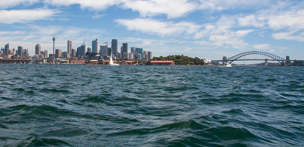 View of the city of Sydney from a boat on Sydney Harbour. Sydney Harbour Bridge is on the right and the Sydney Opera House can be seen to the left of the bridge.