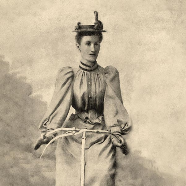 A sepia coloured portrait of a lady on a bicycle. She is dressed in a long sleeved blouse and long dress as worn by bicycle tourists in 1894.