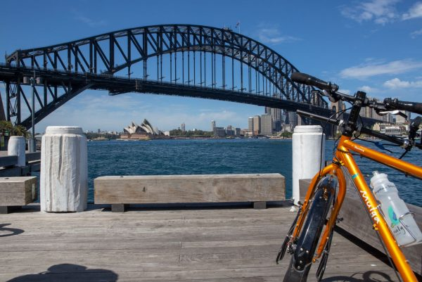 A gold bicycle with a Mulga Bicycle Tours water bottle leans against a wharf pylon with Sydney Harbour Bridge and Sydney Opera House in the background.