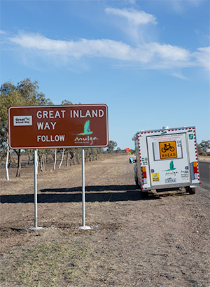 "A road side sign reads ""Great Inland Way Follow Mulga. The Mulga trailer is parked beside the sign with a ""Cyclists Ahead"" warning sign on the back."