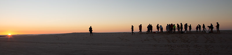 Silhouettes of people against an orange and salmon sky watching the sunset over the Gulf of Carpentaria.