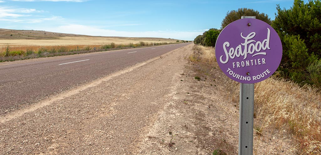 "Purple disc shaped sign beside the Flinders Highway. The sign reads ""Seafood Frontier Touring Route""."